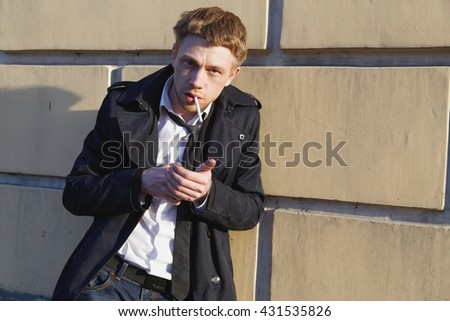 Gorgeous man in a raincoat standing in front of a brick wall. Blond. lights a cigarette