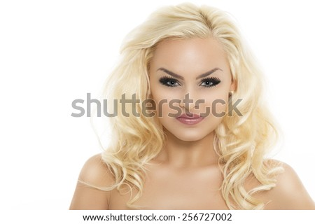 Gorgeous naked blond woman with smiling eyes and lovely curly long hair looking directly into the camera with a gentle smile, head and shoulders isolated on white