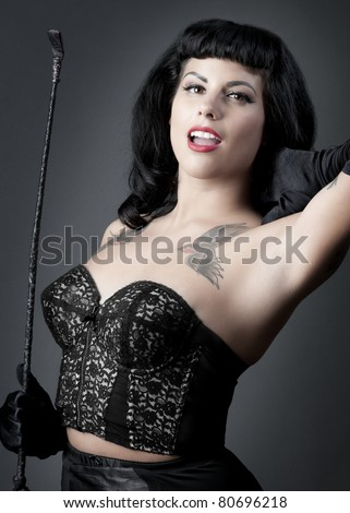 Gorgeous pin up model in sexy black lingerie holding riding crop - stock photo