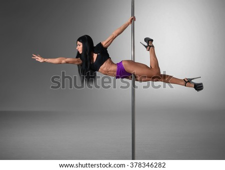 gorgeous pole dancer making trick - stock photo