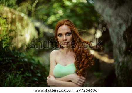 Gorgeous redhead girl in cloudy mint dress in medieval castle - stock photo