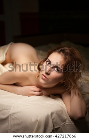Gorgeous redhead lying naked in bed looking at camera. Sensuality and sexuality - stock photo