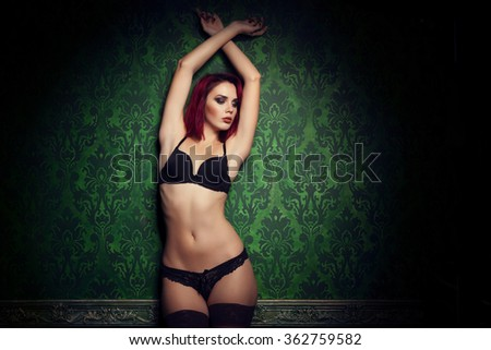 Gorgeous redhead with perfect body in lingerie on green vintage pattern background - stock photo