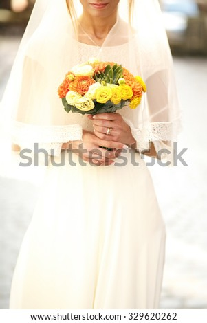 gorgeous romantic happy bride holding beautiful colorful bouquet on the background of old sunny city