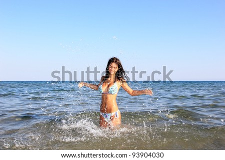 gorgeous sexy woman splashing in ocean