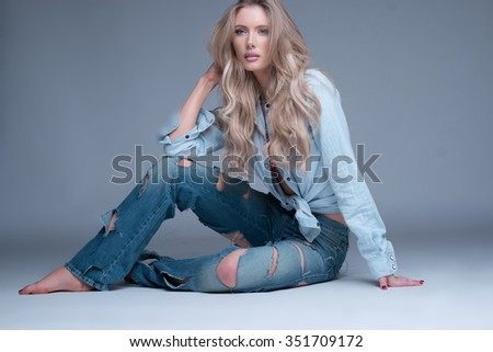Gorgeous slender young trendy blond woman in slashed designer jeans sitting barefoot relaxing on the floor looking at the camera with a serious expression - stock photo