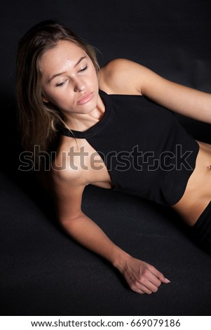 Gorgeous slim woman in sport clothes in studio photo on black background. Healthy and lifestyle