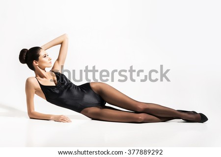 Gorgeous, slim woman posing in alluring underwear and stockings over isolated background. - stock photo
