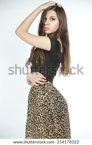 Gorgeous slim young brunette with her hair down wearing high waisted black leopard skirt with a black top on a white background in a studio. - stock photo