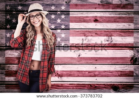 Gorgeous smiling blonde hipster posing against composite image of usa national flag - stock photo