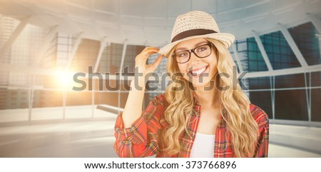 Gorgeous smiling blonde hipster posing against modern room overlooking city - stock photo