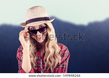 Gorgeous smiling blonde hipster posing with sunglasses against blurred mountains