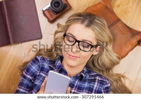 Gorgeous smiling blonde hipster using smartphone and lying on wooden floor - stock photo