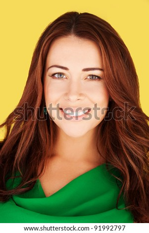 Gorgeous smiling redhead woman with lovely complexion and subtle makeup, close-up portrait on yellow - stock photo