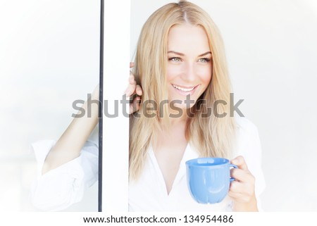 Gorgeous smiling woman standing near open window at home and enjoying tasty beverage, morning coffee, happiness concept