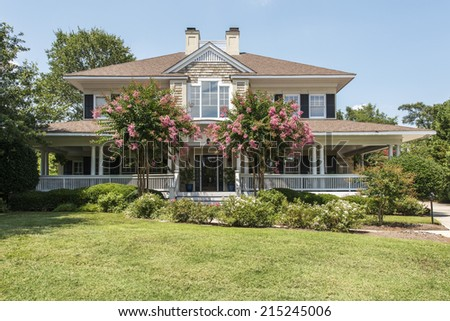 Gorgeous southern home with wrap around white porch and blooming crepe myrtle trees - stock photo