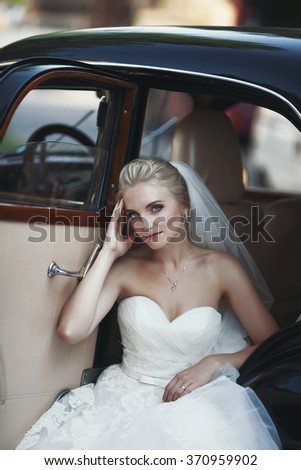 Gorgeous stylish blonde bride posing in retro black car in white dress - stock photo