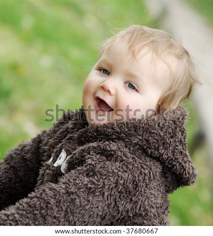 gorgeous toddler laughing in park - stock photo