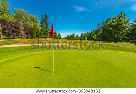 Gorgeous view at the beautiful golf course with sand bunker and red flag. - stock photo