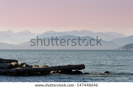 Gorgeous view at the marine scenery. Ocean inlet  with some logs and the mountains and hills as a great background. Vancouver, Canada. - stock photo