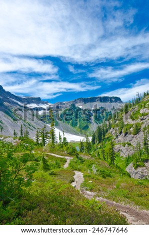 Gorgeous view at the mountain valley with trail, lake and snow. North America. Vertical. - stock photo