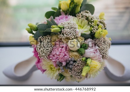Gorgeous wedding bouquet made of pink and yellow flowers stands behind white shoes - stock photo