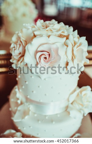 Gorgeous wedding cake decorated with huge white roses - stock photo