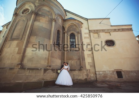 gorgeous wedding couple enjoys a Sunny day in the old town with architecture