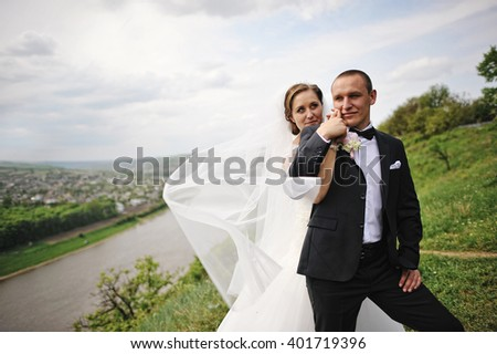 Gorgeous wedding couple on the hill with river and beautiful landscape