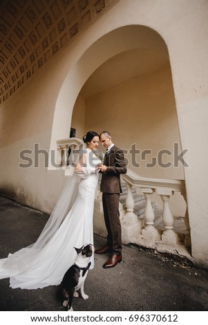 Gorgeous wedding couple walking in the old city with dog. Classical architecture