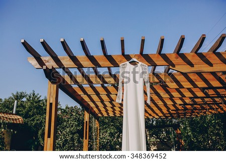 gorgeous wedding dress hanging outside on a sunny day - stock photo