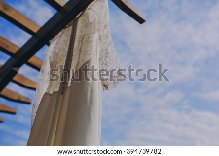 gorgeous wedding dress hanging outside on a sunny day
