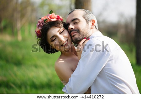 Gorgeous wedding portrait. Young handsome groom with beard in white shirt hugs his beautiful brunette bride with flowers in her hair. Sincere feelings and emotions. Tender wedding closeup.  - stock photo