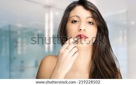 Gorgeous woman applying lipstick - stock photo
