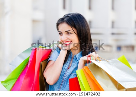 Gorgeous woman holding shopping bags and smiling joyfully after a shopping.