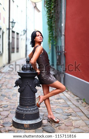 Gorgeous woman in beautiful dress is leaning with her back against old column in sexual and beautiful pose on the street of Old Riga, Latvia - stock photo