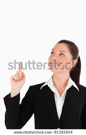 Gorgeous woman in suit pointing at a copy space while standing against a white background - stock photo