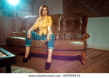 gorgeous woman in yellow unbuttoned jacket posing on a leather couch looking away