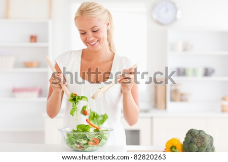 Gorgeous woman mixing a salad in her kitchen - stock photo