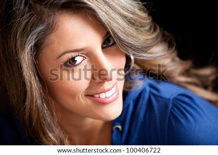 Gorgeous woman portrait smiling - isolated over a black background - stock photo