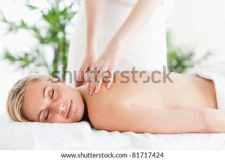 Gorgeous woman relaxing on a lounger during massage with eyes closed in a wellness center - stock photo