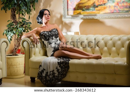 Gorgeous woman sitting on a leather beige sofa - stock photo