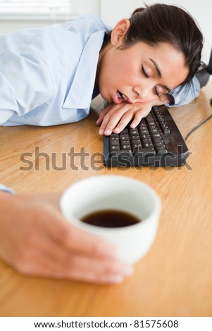 Gorgeous woman sleeping on a keyboard while holding a cup of coffee at the office - stock photo