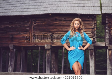 Gorgeous woman wearing a sexy blue asymmetric  tight dress in a conceptual natural village environment on the porch of an old wood chalet. Beautiful  model posing sensual - stock photo