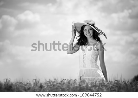 Gorgeous woman with hat enjoying in wheat field