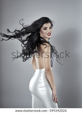 Gorgeous woman with long curly hair posing on gray background