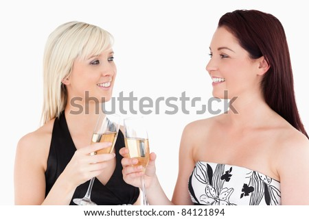 Gorgeous women in beautiful dresses toasting with champagne in a studio