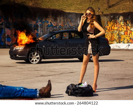 Gorgeous young adult female stand near bag full of money behind burning car outdoors - stock photo
