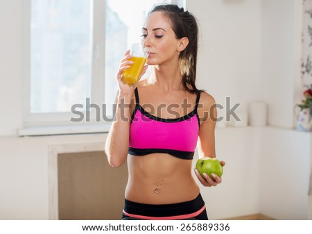 Gorgeous young athletic sportive woman in sport outfit drinking fruit juice after the training. - stock photo