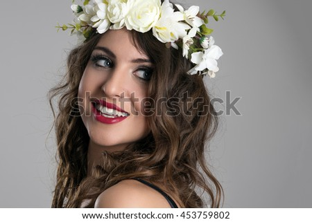 Gorgeous young beauty model looking back over the shoulder smiling on gray studio background - stock photo
